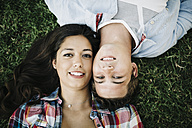 Portrait of young couple in love lying head to head on a meadow - JRFF000115