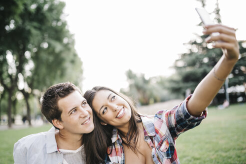 Portrait of young couple in love taking a selfie with smartphone in a park - JRFF000121