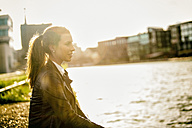 Germany, Muenster, young woman relaxing at city harbour in evening twilight - TAMF000282