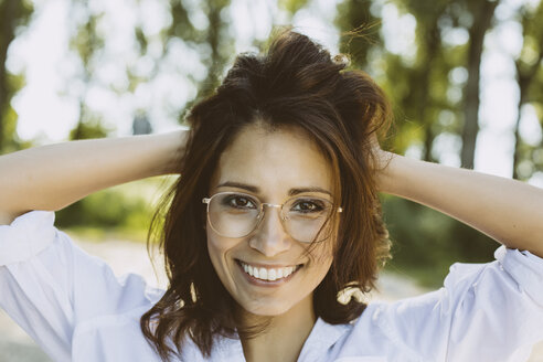 Portrait of smiling woman with hands in her hair wearing glasses - MFF002254