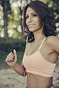 Portrait of smiling woman with earphones jogging - MFF002263