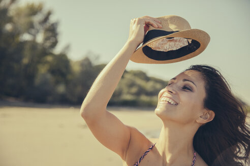 Portrait of happy woman lifting her hat on the beach - MFF002272