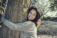 Portrait of smiling woman with closed eyes hugging a tree - MFF002275