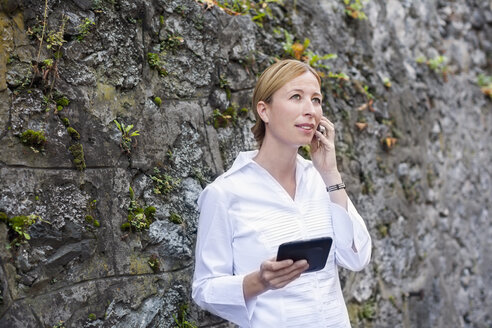 Blond woman standing in front of rock face telephoning with smartphone - NNF000298