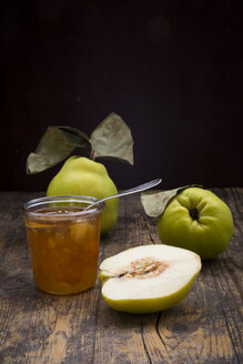 Whole and sliced quinces and a glass of quince jam on wood - LVF003983