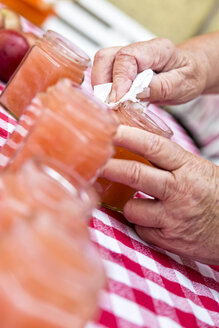 Senior woman wiping glass of homemade applesauce, close-up - MIDF000694
