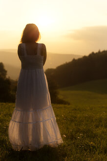Germany, Baden-Wuerttemberg, Black Forest, back view of woman on Alpine meadow watching sunrise - MIDF000700