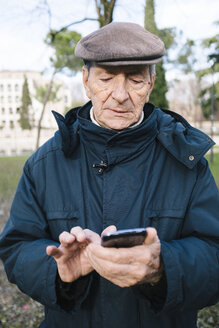 Portrait of senior man with smartphone in a park - GIOF000273