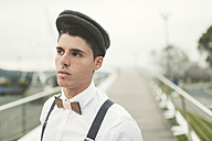 Portrait of young man wearing beret and a wooden bow tie - RAEF000537