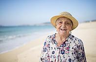 Spain, Ferrol, portrait of happy senior woman standing on the beach - RAEF000541