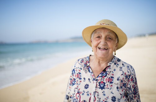 Spain, Ferrol, portrait of happy senior woman standing on the beach - RAEF000541