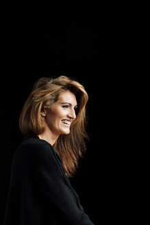 Portrait of smiling woman with brown hair wearing black clothes in front of black background - CHAF001516