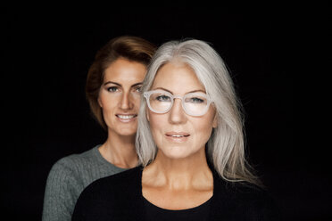 Portrait of mature woman and younger woman standing behind her in front of black background - CHAF001522