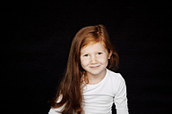 Portrait of redheaded smiling little girl in front of black background - CHAF001525