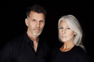 Portrait of mature man and mature woman wearing black clothes in front of black background - CHAF001531