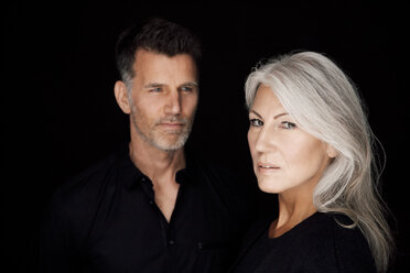Portrait of mature man and mature woman wearing black clothes in front of black background - CHAF001534