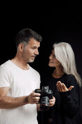 Man and woman with camera in front of black background - CHAF001546