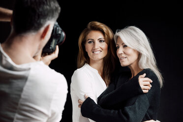 Man photographing two women in front of black background - CHAF001549