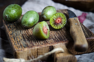 Sliced and whole mini kiwis and kitchen knife on wooden chopping board - SBDF002301