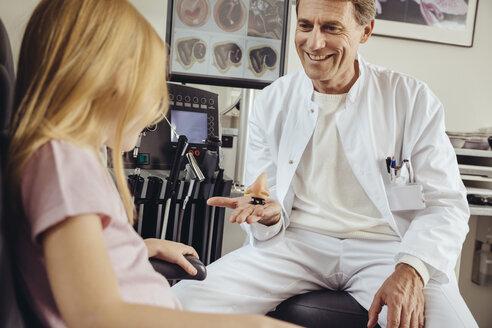 Doctor explaining running nose to little girl - MFF002298