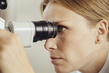 Profile of female doctor looking through surgical microscope - MFF002310