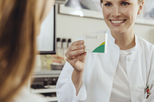 Doctor showing patient medication - MFF002316