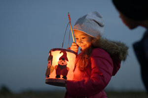 Smiling little girl with self-made paper lantern in the evening - LBF001245