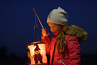 Portrait of little girl with lighted paper lantern on St. Martin's Day at twilight - LBF001249