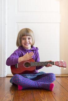 Portrait of little girl sitting on wooden floor playing ukulele - LVF003988