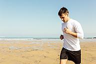 Spain, Asturias, Gijon, young man running on the beach - MGOF000841