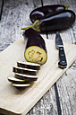 Aubergines on chopping board, knife - LVF003995