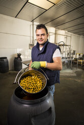 Worker in food processing plant holding bucket with olives - JASF000152