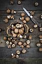 Crimini mushrooms in basket, pocket knife on wood - LVF004002