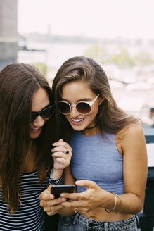 USA, New York City, two smiling friends looking at cell phone - GIOF000279
