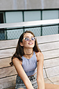 Brunette young woman wearing sunglasses relaxing on bench - GIOF000294