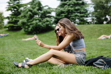 Two happy friends in a park looking at cell phone - GIOF000315