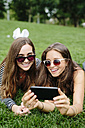 Two happy friends in a park looking at cell phone - GIOF000318