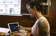 Tattooed young woman sitting in a coffee shop using digital tablet - MGOF000850