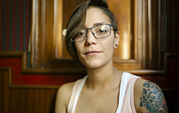 Portrait of tattooed young woman wearing glasses - MGOF000853