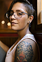 Portrait of tattooed young woman with nose piercing wearing glasses - MGOF000856