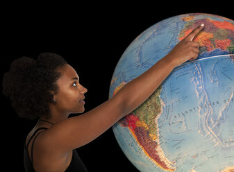 Young woman pointing on large globe - KLR000250