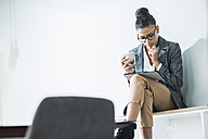 Young woman in office with cup of coffee and digital tablet - UUF005800