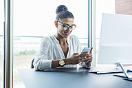 Smiling young woman in office looking on cell phone - UUF005821