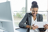 Smiling young woman in office looking on digital tablet - UUF005827