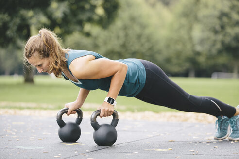 Young woman going pushups on kettlebells - MADF000549