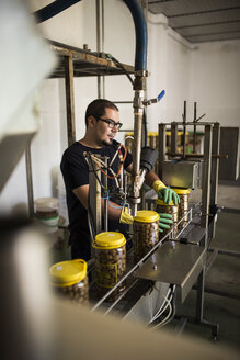 Man in factory at conveyor belt with filled olive glasses - JASF000167