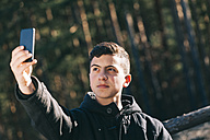 Portrait of teenage boy taking a selfie with his mobile phone - BZF000268