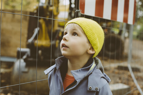 Portrait of little boy with yellow woolly hat in front of construction site - MFF002373