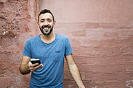 Portrait of smiling bearded man with smartphone - RAEF000555