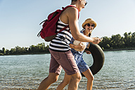 Young couple with inner tube and cell phone walking at the riverside - UUF005850